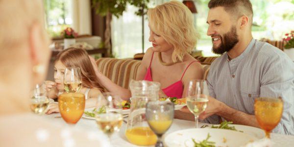 Loving mommy. Loving blonde-haired mommy touching head of daughter while having family lunch