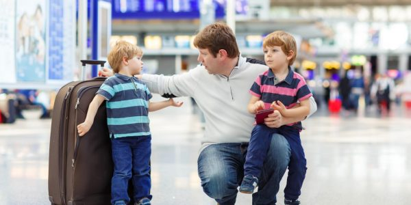 man at airport with kids